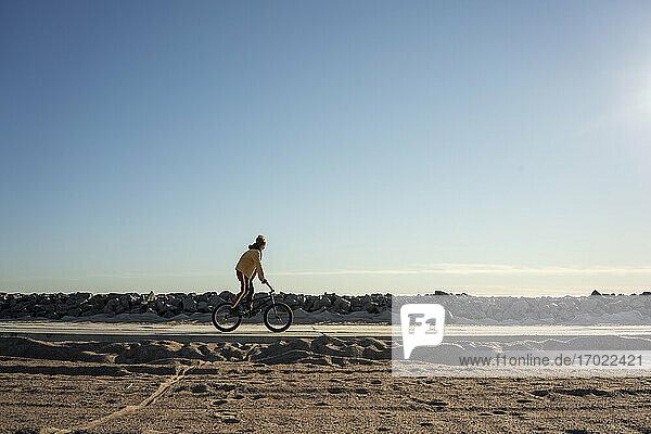 Klarer Himmel über einem Jungen  der BMX auf einer leeren Straße fährt Klarer Himmel über einem Jungen, der BMX auf einer leeren Straße fährt