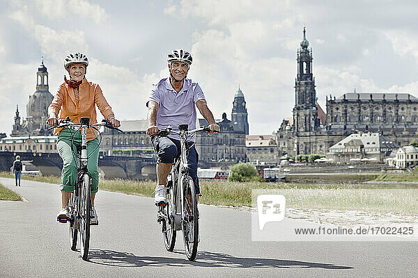 Smiling senior exploring Frauenkirche on electric bicycle at Dresden  Germany