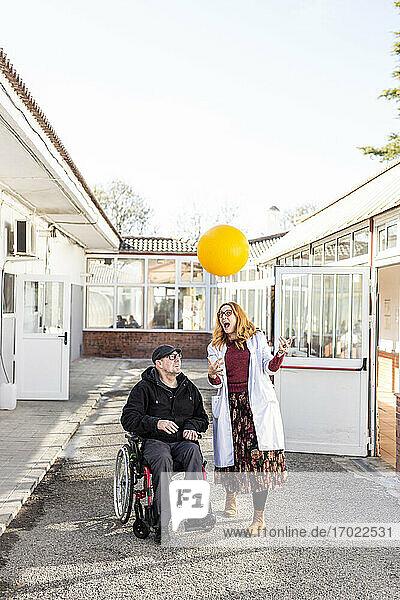 Krankenschwester und behinderter Mann spielen mit Ball gegen den Himmel vor einem Pflegeheim