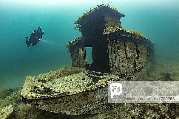 Scuba diver swimming toward shipwreck sunken in Lake Atter