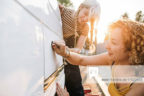 Young female couple working on their van