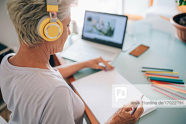 Woman taking online art course at home