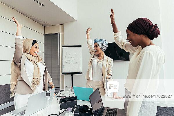 Businesswomen raising arms together