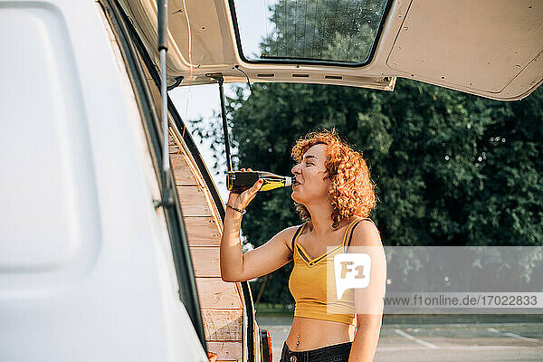 Young woman having a beer at the back of a van