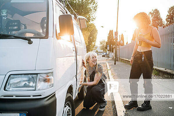 Young female couple working on van and having a beer