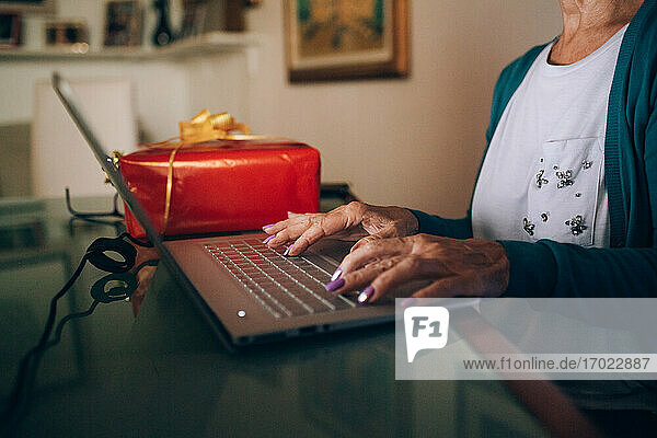 Woman using laptop with Christmas Property Released (PR)esent beside her