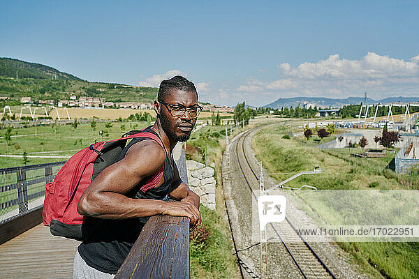 Young man on bridge by railway track