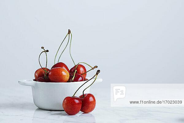 Frische Kirschen mit Stielen im Keramiktopf auf Marmortisch