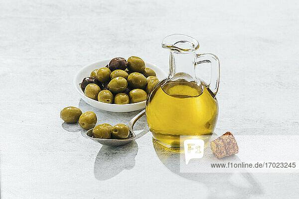 Olivenöl im Glaskrug neben grünen Oliven