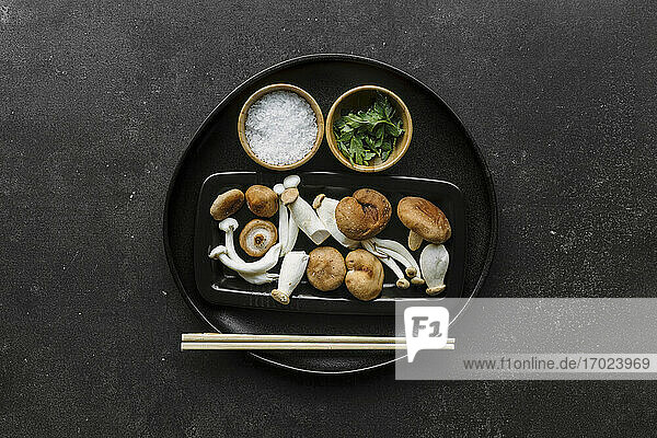 Verschiedene rohe Pilze  Salz  Petersilie und Essstäbchen auf schwarzem Teller