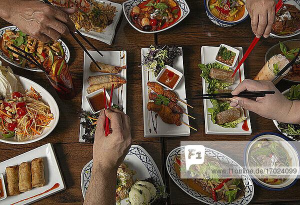 Verschiedene pikante thailändische Speisen auf Holztisch  Hände mit Essstäbchen