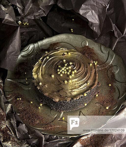 Schokoladenkuchen mit Creme und goldenen Zuckerperlen