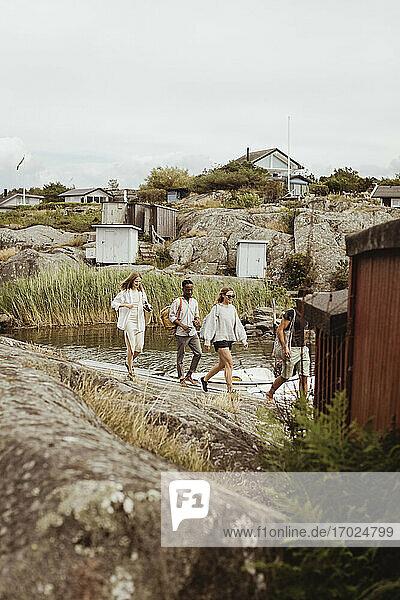 Friends walking on rock by sea at marina during summer vacation