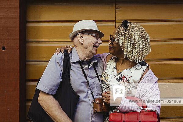 Lächelnde Senior Paar mit Armen um gegen die Wand