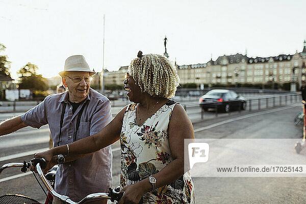 Fröhliches Paar mit Fahrrad auf der Straße in der Stadt