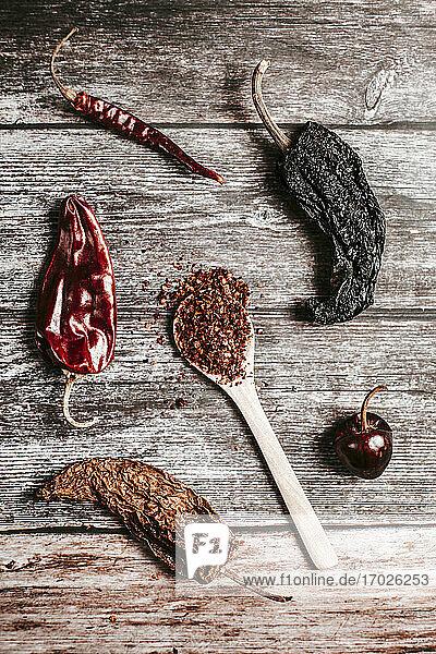 Verschiedene getrocknete Peperoni und Chilipulver auf Holzlöffel
