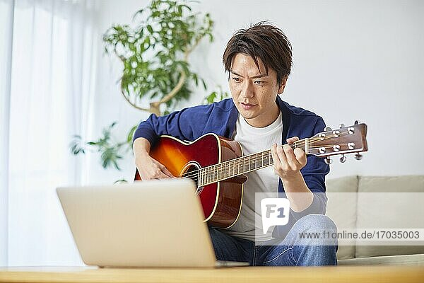 Japanese man playing guitar at home