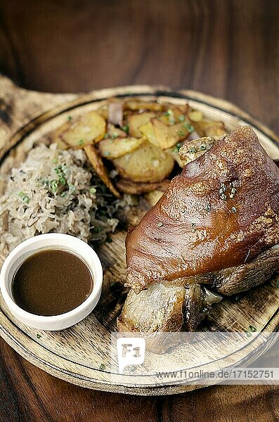 SCHWEINSHAXE traditional german pork knuckle with sauerkraut and potatoes bavarian meal on rustic wood background.