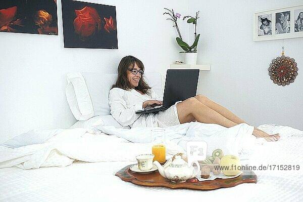 Frau frühstückt und arbeitet mit ihrem Computer im Bett...