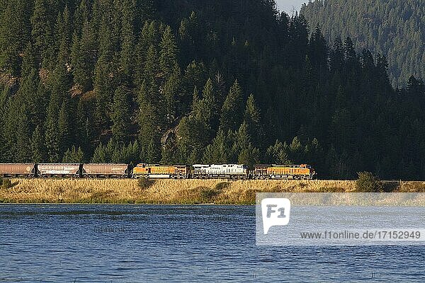 A Montana Rail Link train running BNSF locomotives by Lake Pend Oreille in north Idaho  United States.