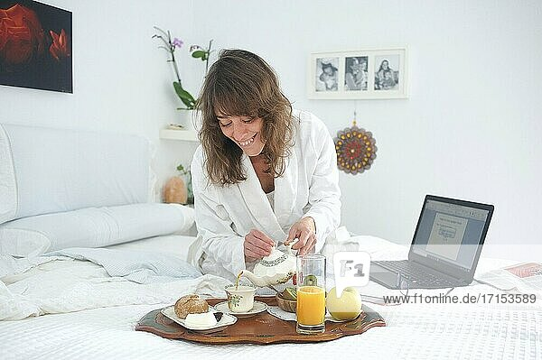 Woman having breakfast and working with her computer in bed...