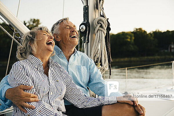 Cheerful couple laughing while spending leisure time in sailboat