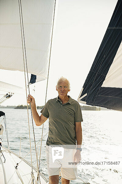 Portrait of senior man holding rope while standing in boat against sea on sunny day