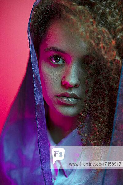 Junge modische Frau mit Schal um das Haar gegen rosa Hintergrund
