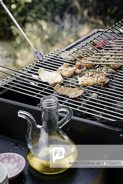 Olive oil jar kept besides barbecue grill in back yard