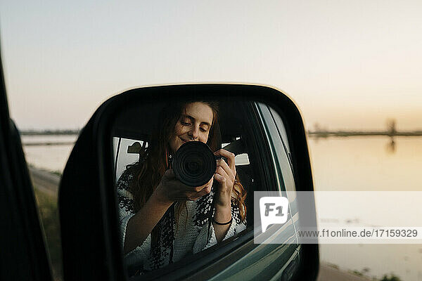 Young woman photographing self on side-view mirror reflection through camera at Ebro Delta