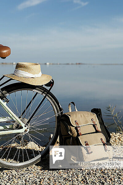 Sun hat kept on bicycle by backpack against sky on sunny day at Ebro Delta  Spain