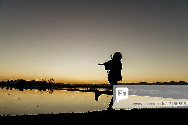 Young woman twirling on one leg during sunset at Ebro Delta  Spain