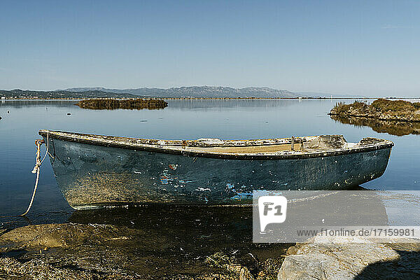 Abandoned rowboat moored in lake against clear sky on sunny day at natural park  Ebro Delta  Spain