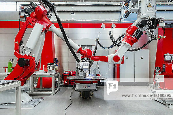 Automated industrial robots welding metal in factory