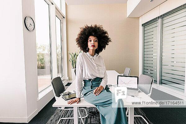 Portrait of businesswoman sitting on desk in office