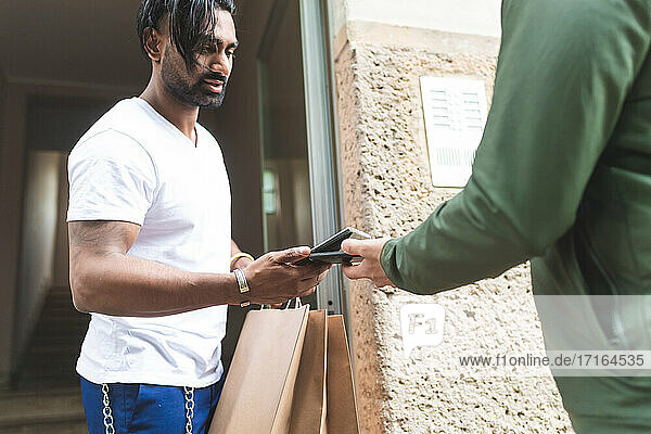 Man collecting takeaway delivery  using contactless payment on phone