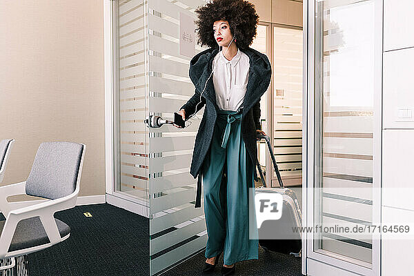 Businesswoman arriving in office with suitcase
