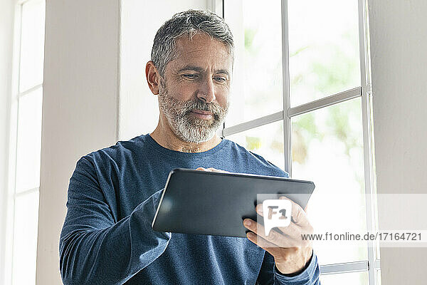 Smiling businessman working on digital tablet while standing at home