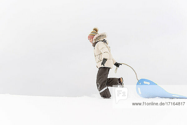 Girl pulling sled while walking on snow covered land against sky