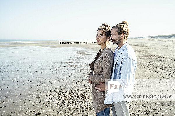 Junges Paar träumt zusammen am Strand stehend Junges Paar träumt zusammen am Strand stehend
