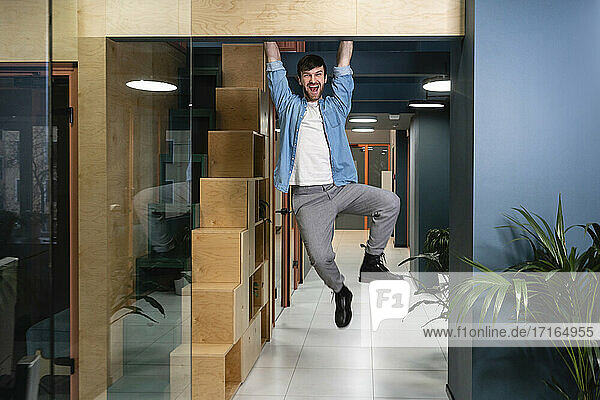 Cheerful businessman hanging at doorway at work place