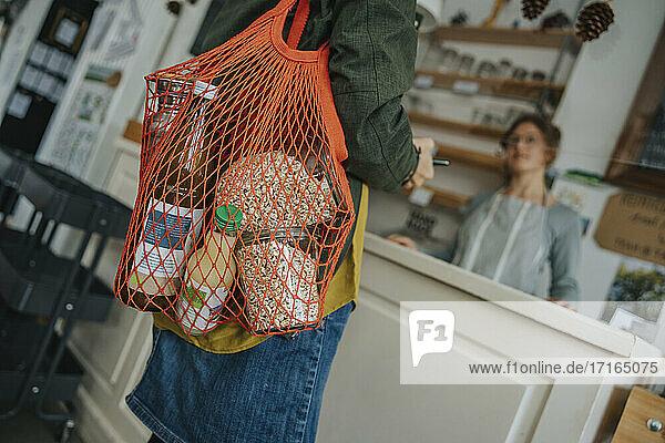 Female customer carrying mesh bag full of groceries in retail store