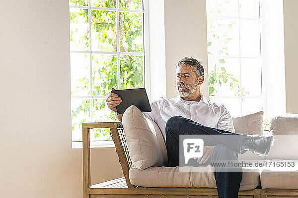 Entrepreneur using digital tablet while working at home