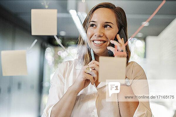 Nahaufnahme einer lächelnden Geschäftsfrau  die über ein Smartphone im Büro spricht  gesehen durch eine Glaswand