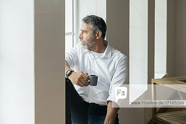 Thoughtful businessman with coffee cup looking through window while sitting at home