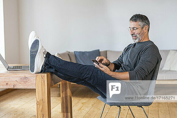 Smiling businessman using mobile phone while sitting at home office