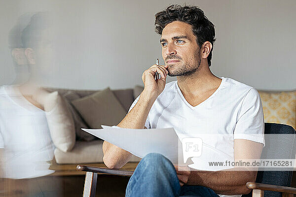 Thoughtful man with hand on chin while sitting at home