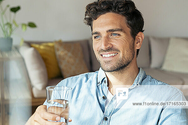 Mid adult man holding glass while sitting at home