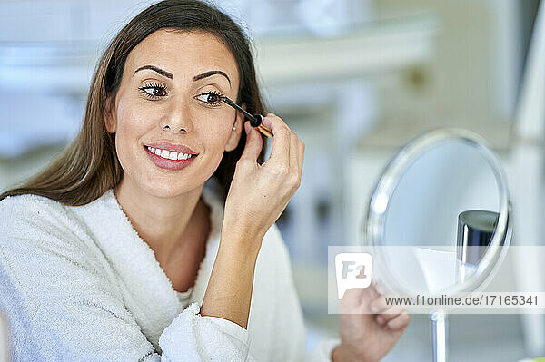Smiling woman applying mascara while looking in mirror at home