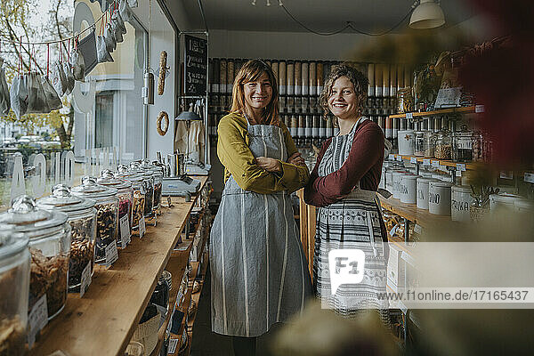 Smiling female coworkers with arms crossed standing in retail shop
